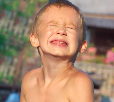痛みを作る子供男の子泣いて顔子牛を示す