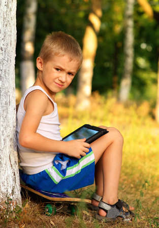 Boy Child playing with Tablet PC sitting on skateboard Outdoor with forest on background Game Dependence concept photo