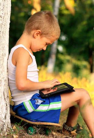 Niño del muchacho que juega con el Tablet PC al aire libre con el bosque en el fondo Computer concepto de dependencia del juego Foto de archivo