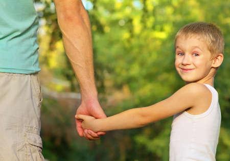 Familia Padre Hombre e Hijo del niño del muchacho que sostiene la mano al aire libre emoción felicidad con la naturaleza del verano en el fondo