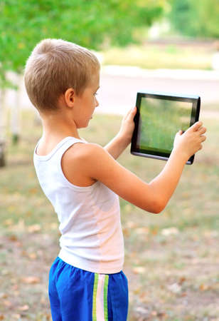 Boy Child playing with Tablet PC standing Outdoor with nature on background Computer Game Dependence concept photo