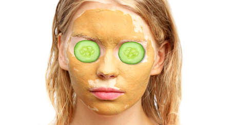 Spa Woman Face with facial Clay Mask Organic Beauty treatments Skin Care with cucumber slices on eyes isolated on white background photo