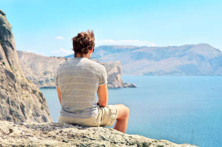 Young Man relaxing on rocky cliff sitting and looking on Sea and mountains Summer time Freedom concept photo