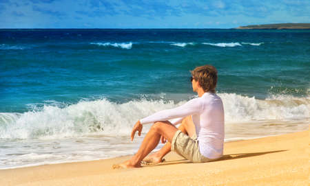 Handsome Man relaxing on the Beach sitting on seaside sand and looking on Sea waves Summer time Freedom and Happiness concept