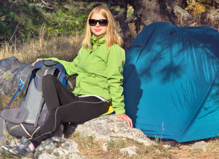 Young Woman with Smiling Face Hiker sitting with backpack and Tent Camping Outdoor on Grass with forest nature on background Travel and Healthy Lifestyle concept photo