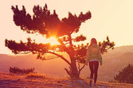 Árvore só na montanha e mulher andando sozinha em Sunset trás vista nas cores laranja e rosa Melancholy solidão conceito emoções Banco de Imagens