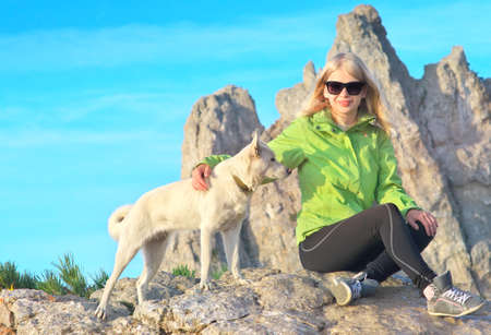 Smiling Woman Traveler and white dog sitting on stones relaxing with Rocky Mountain peak Ai-Petri and blue sky on Background Traveling Climbing concept photo