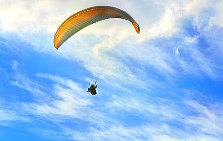青い空と雲の背景の健康的なライフ スタイルと自由の概念のパラグライダー極端なスポーツ 写真素材