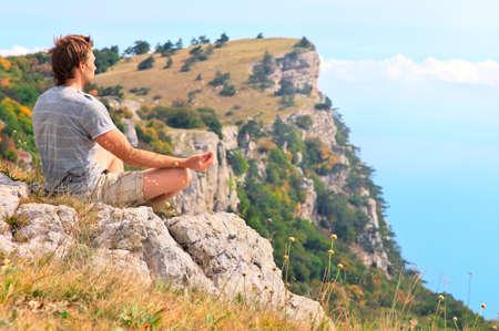 男子旅行者放鬆瑜伽冥想坐在沙發上與落基山脈的石頭和藍天的背景與自然和諧相處的理念