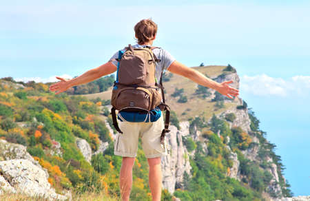 Man Traveler with backpack standing outdoor hands raised to the blue sky with mountains on background Freedom and Healthy Lifestyle Hiking concept photo