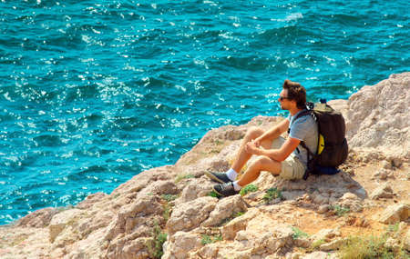 Young Man with backpack relaxing on rocky cliff with blue Sea on background Summer Traveling and Healthy Lifestyle concept