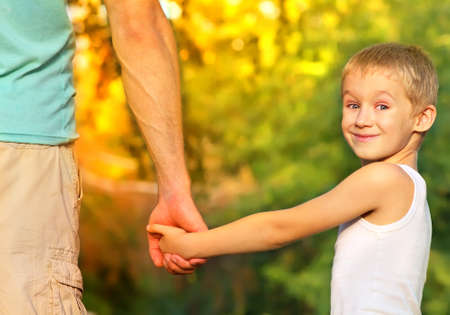 Happy Family Father Man and Son Boy Child holding hand in hand Outdoor with summer nature on background Parents and Children relationship concept