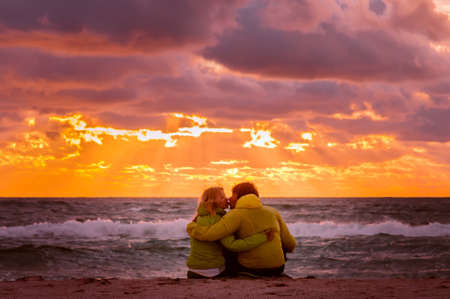 美しい夕焼け空風景人ロマンチックな関係概念とビーチの海辺にハグとキスの愛のカップルの男女