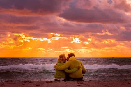 夫婦男人和女人在愛接吻和擁抱在沙灘海濱與美麗的夕陽的天空的風景人的浪漫關係的概念
