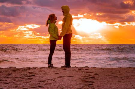 ビーチ シーサイドを保持している手に美しい夕焼け空風景人のロマンチックな関係および友情の概念の上に立っている愛のカップルの男女