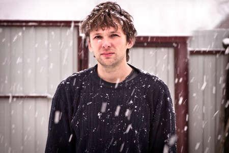 Jeune homme dans le chandail avec des flocons de neige debout en plein air saison d'hiver Neige météo style branché Banque d'images