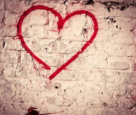urban colors: Mano roja del amor del corazón dibujado en la pared de ladrillo del grunge textura de fondo, estilo de la calle de moda