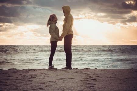 아름 다운 석양 하늘 풍경 사람들 로맨틱 한 관계와 우정 개념 유행 변덕 색상으로 손에 비치 해변 손을 잡고 몇 서있는 남자와 사랑에 여자
