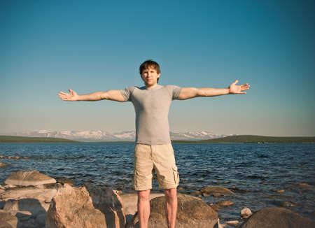 hands raised: Handsome Man young standing Outdoor hands raised Freedom  Lifestyle Traveling concept with lake and mountains on background scandinavian nature