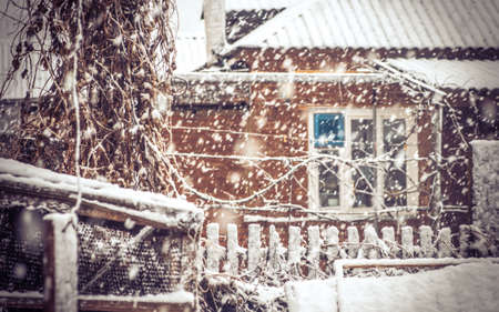 Snowfall Winter Weather in village with snowflakes and old house window moody seasonal scene Snow storm with trendy colors photo