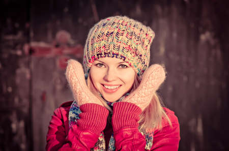 Young Woman Beautiful happy smiling Face Winter time wearing knitted hat and scarf with mittens Lifestyle concept and Christmas holiday trendy colors photo