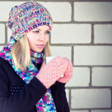 Young Woman with cofee cup Winter time wearing knitted sweater, hat and scarf with mittens Lifestyle concept trendy colors with white brick wall on background photo