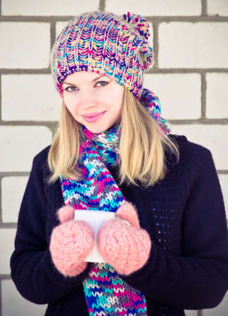 Smiling Woman with coffee cup Winter time wearing knitted sweater, hat and scarf with mittens Lifestyle concept with white brick wall on background photo