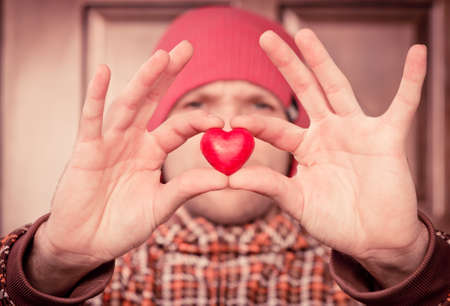 greeting people: Heart shape love symbol in man hand with face on background Valentines Day romantic greeting people relationship concept winter holiday Stock Photo