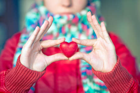 greeting people: Heart shape love symbol in woman hands with face on background Valentines Day romantic greeting people relationship concept winter holiday