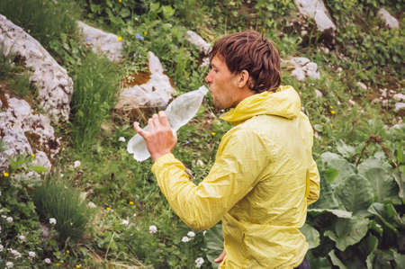 Man drinking cold water holding plastic bottle in mountains with green nature on background Summer Traveling Hiking