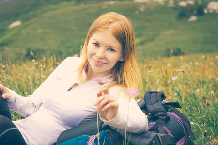 Woman traveler relaxing outdoor on green valley with flowers enjoying nature with backpack hiking traveling film effect colors photo