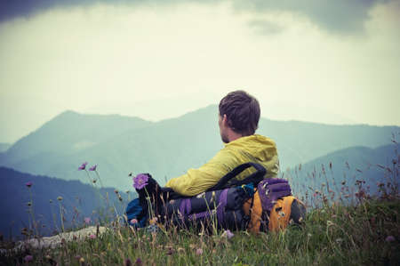 Man Traveler com a trouxa de relaxar com montanhas no fundo do ver