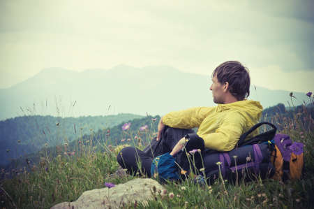 Man Traveler with backpack relaxing with Mountains on Background Summer Traveling Outdoor Stock Photo