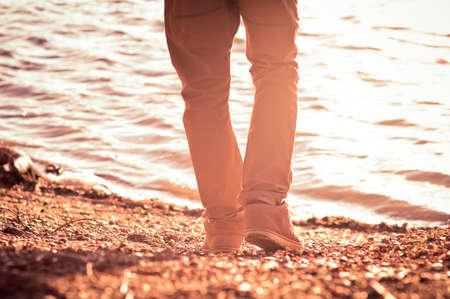 ビーチのトレンディなスタイルの憂鬱な概念上屋外を歩いて男を足します。
