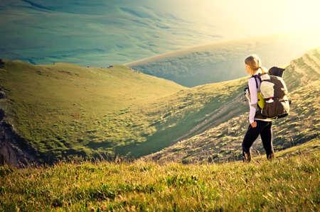 Женщина путешественник с рюкзаком в поход в горы с красивым летний пейзаж на альпинизма спорта концепции образа жизни Фото со стока