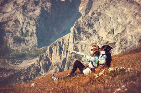 Woman Traveler with Backpack relaxing in Mountains with rocks on mountaineering hiking sport lifestyle concept