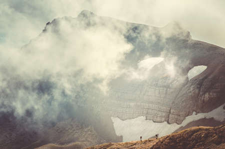 Rocky Mountains with clouds and hikers silhouette beyond beautiful Landscape Caucasus nature