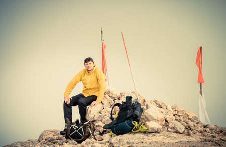 Man Traveler on Mountain summit with backpack Traveling Mountaineering concept fog  photo