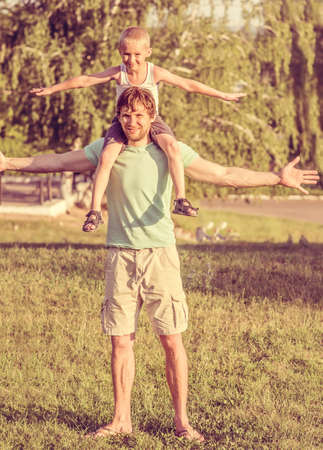 toning: Family Father Man and Son Boy sitting on shoulders Outdoor Happiness emotions Lifestyle with summer nature on background