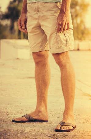 ショート パンツや屋外の夏の休暇のライフ スタイルのコンセプトに立ってのフリップフ ロップを着て男足 写真素材