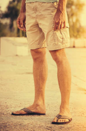 Man Feet wearing shorts and flip flops standing Outdoor summer vacations lifestyle concept Imagens