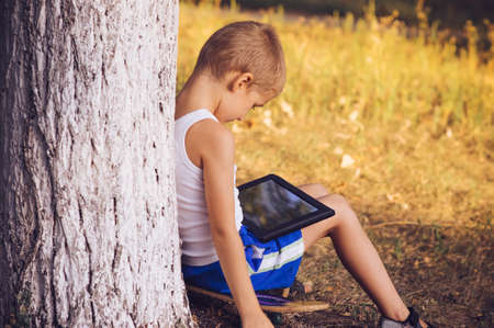 夏の自然背景コンピューター ゲーム依存性概念のライフ スタイルにタブレット PC 屋外で遊ぶ男の子の子供