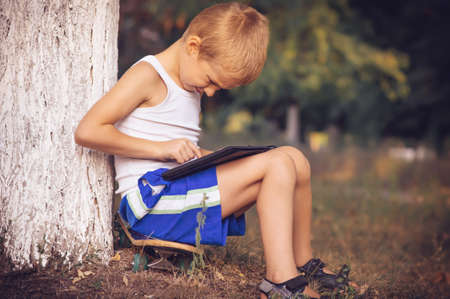 Boy Child playing with Tablet PC Outdoor with Summer nature on background Computer Game Dependence concept Lifestyle photo