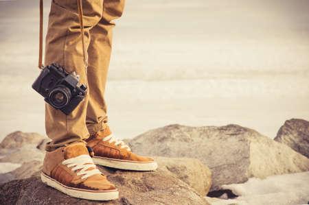 Fötterna man och retro fotokamera Travel utomhus Livsstil semester koncept Stockfoto