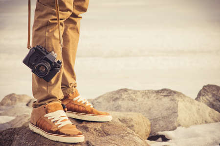 vacation: Feet man and vintage retro photo camera outdoor Travel Lifestyle vacations concept