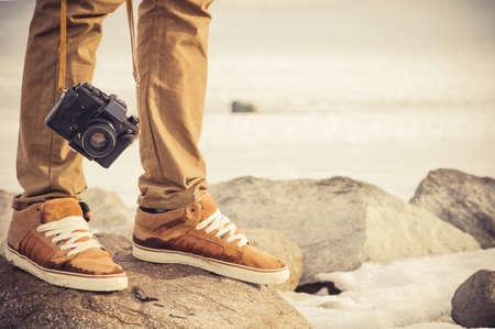 Pieds homme et vintage caméra photo rétro vacances en plein air de style de vie de Voyage notion Banque d'images
