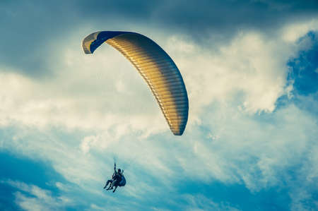 parachuting: Paragliding extreme Sport with blue Sky and clouds on background Healthy Lifestyle and Freedom concept Summer Vacations