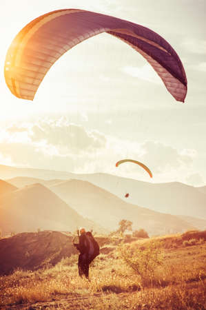parasailing: Paragliding extreme Sport with mountains on background Healthy Lifestyle and Freedom concept Summer Vacations Stock Photo