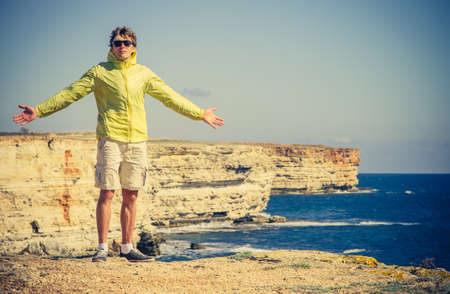 Man Traveler with raised hands outdoor Sea and Rocks coastal on background Freedom Lifestyle concept photo