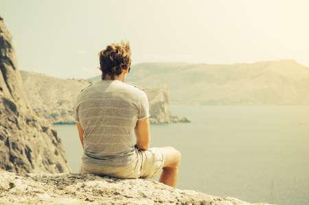 Homem novo que relaxa no penhasco rochoso mar e as montanhas no fundo estilo de vida das férias de verão conceito cores retros